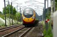 With a slight heat shimmer surrounding it, a northbound Virgin Pendolino races along the straight approaching Bolton-le-Sands LC on 19 June 2010.<br><br>[John McIntyre&nbsp;19/06/2010]