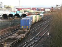 A class 66 locomotive shunting a container train from the W H Malcolm Grangemouth depot in January 2006. View is north towards the site of the former Grangemouth station, with Fouldubs Junction behind the camera. The chimney of Longannet power station, standing on the other side of the Forth, is prominent in the background.<br><br>[John Furnevel&nbsp;24/01/2006]