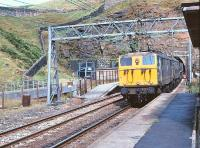 View from the staggered westbound platform at the closed Woodhead Station on 15 August 1979 as 76034+76031 emerge from Woodhead tunnel with a Trans - Pennine coal train.<br><br>[Peter Todd&nbsp;15/08/1979]