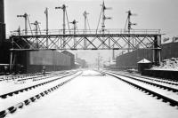 A scene which had been largely silent for several months by the time this winter 1965-66 shot was taken - looking west mid-way between Princes Street station and Dalry Junction along the closed Caledonian main line in Edinburgh. The only surviving traffic was trip workings to the Morrison Street coal yard, using the tracks on the far right, which ceased just a few months later.  <br> Part of the Scottish & Newcastle brewery complex on Fountainbridge is on the left and Dalry Junction signal box can be seen in the distance. Nowadays this view is dominated by the Western Approach Road and the brewery is long gone<br> <br><br>[David Spaven&nbsp;//1965]