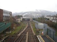 Looking towards Treherbert from Porth station on 31 January 2012. On the left is the former down track, now a long siding. The route is now single track forward to Treherbert, apart from the passing loop at Ystrad Rhondda. Token operation applies from Porth to Ystrad Rhondda and from there to Treherbert. The path running forward to the right of the railway is on the trackbed of the former Maerdy branch which ran under the right hand side of the road overbridge.<br><br>[David Pesterfield&nbsp;31/01/2012]