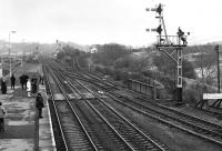 Looking east from the station footbridge at Haltwhistle on a grey 27 March 1976. The Alston branch curves away on the climb towards the viaduct over the South Tyne on the right, while a healthy complement of passengers waits on the staggered eastbound platform for the next service to Newcastle.<br><br>[Bill Jamieson&nbsp;27/03/1976]