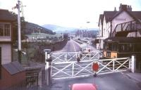View from the top deck of a bus stopped at Conwy Road level crossing in the 1960s looking south west towards Conwy Castle. A Rhyl bound DMU off the Llandudno branch is about to run over the crossing and will shortly arrive at Llandudno Junction station off picture to the left. The scene no longer exists, with the level crossing now replaced by a flyover, the signal box long gone, the pub on the right (the 'Maelgwyn') demolished etc ..etc. [see image 36849]<br><br>[Ian Dinmore&nbsp;//]
