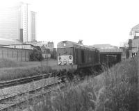 A southbound freight passes West Brompton LT station in June 1969 hauled by EE Type 1 locomotive no D8000. Photograph taken leaning over the fence alongside the northbound District Line platform 2, with the western edge of Earl's Court Arena visible on the right beyond the station roof. At that time the West London Line was still very much a cross-London freight corridor with no hint of the changes that would take place here 30 years later [see image 5126].<br><br>[John Furnevel&nbsp;05/06/1969]