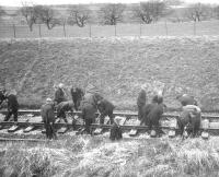 Another shot of the Permanent Way squad at work on Easter Sunday 1963 during the reballasting of Kilruskin cutting near West Kilbride [see image 37966]. Note the preferred headgear of the day.<br><br>[R Sillitto/A Renfrew Collection (Courtesy Bruce McCartney)&nbsp;14/04/1963]