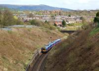 A First TransPennine Express Class 185 on a service to Manchester Airport enters Chorley as it leaves the deep cutting on the north side of the town on 31 March 2012. Beneath the photographer is Chorley Tunnel and in the background is Rivington Pike on the West Pennine Moors.<br><br>[John McIntyre&nbsp;31/03/2012]