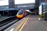 An up Pendolino passing Nuneaton platform 4 at about 100mph on 1 April 2012. Notice the cut-back end of platform 3 on the left - this was damaged by the sleeper derailment in 1975 and has never been restored. Notice also the contrast between the original cross-station footbridge and the extension spanning the recently built platforms 6 and 7 to the right.<br><br>[Ken Strachan&nbsp;01/04/2012]