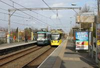A contrast between a twenty year old 1000 series tram and its 3000 series successor at Timperley in March 2012. Under an original pre-war gantry 3002 runs in on an Altrincham bound service while 1022 heads for Piccadilly. Some of the 10xx trams are to be withdrawn as a source of spares to keep sister units running as they are proving somewhat troublesome in later life.<br><br>[Mark Bartlett&nbsp;08/03/2012]