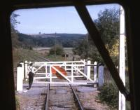 A member of the train crew opens the crossing gates between Staverton and Totnes on 30 July 1969 on what was then the Dart Valley Railway. The view is from the front of the Auto coach of the train in which the locomotive, an ex GWR 0-6-0 Pannier Tank, was sandwiched between 4 coaches.<br><br>[John McIntyre&nbsp;30/07/1969]