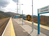 158828 stops briefly at Dovey Junction on the 8 min late 15.03 service to Pwllheli to (not) pick up the photographer who instead had to trek back to his vehicle parked beyond the river bridge at the far end of the 350 metre long Aberystwyth platform.<br><br>[David Pesterfield&nbsp;13/04/2012]