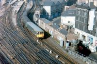A North Tyneside DMU leaving one of the east end bay platforms at Newcastle Central (now part of a car park) in March 1980. Notable in the picture is the old North Eastern Railway 1906 parcels depot in Westgate Road (with the triple pitched roof). [See image 9463]<br><br>[Colin Alexander&nbsp;08/03/1980]
