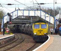 Just before the Duchess was due at Newton-on-Ayr with the <I>'Great Britain V'</I> on 26 April this Killoch - Drax coal train emerged behind 66585, snaking across from the Mauchline line and stopping to collect a crewman. It then crawled through the station blocking all views of the down line and potentially of  the Duchess - causing some anxiety among the waiting paparazzi.  Fortunately it had gone by the time the Pacific appeared. <br><br>[Colin Miller&nbsp;26/04/2012]