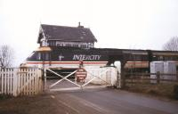 An InterCity 125 speeds over the level crossing at St James Deeping, located on the former GN route between Peterborough and Spalding. The line was in use as a diversionary route in January 1991 during engineering work on the ECML. The instruction on the gate makes an interesting alternative to <I>Pull</I>. [Note: Despite serving the village of Deeping St James, Lincolnshire, the station (closed to passengers in 1961) and signal box both carried the name St James Deeping.] <br><br>[Ian Dinmore&nbsp;27/01/1991]