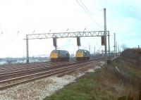 Two early Class 40s at the signal gantry to the south of Preston station in 1980. These signals control the reduction from six tracks to four and 40028, formerly <I>Samaria</I>, on the Up Goods line has been given the road ahead of 40010 once named <I>Empress of Britain</I>. 40028 only lasted another fifteen months in service before withdrawal from Kingmoor but 40010 continued until October 1984 when it was withdrawn from Longsight.  <br><br>[Mark Bartlett&nbsp;08/04/1980]