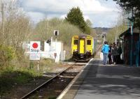 150284 with the 12.07 service on to Swansea runs over the level crossing into Ammanford Station on 11 April to pick up a group of passengers. <br><br>[David Pesterfield&nbsp;11/04/2012]