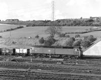 47301 leaves Healey Mills Yard with an eastbound empty colliery trip working in May 1977, overlooked by Ossett's rather austere looking late Victorian isolation hospital at the top of Storrs Hill.<br><br>[Bill Jamieson&nbsp;/05/1977]