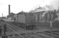 Fowler 4F 0-6-0 no 44462 brings mineral wagons south through Hellifield in February 1965. The locomotive shed stands on the other side of the foot crossing.<br><br>[K A Gray&nbsp;13/02/1965]