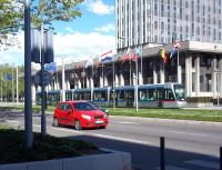 An Alstom Citadis tram on Grenoble's Line C route passes the 1968 Hotel de Ville (like the railway station, a 'legacy' building from the 1968 Winter Olympics) on Boulevard Jean Pain on a fine Sunday afternoon in April 2012.<br><br>[Andrew Wilson&nbsp;29/04/2012]