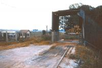 The bulk discharge facility at the end of the long private siding that ran from Alness station to Dalmore distillery, seen here in 1974, by which time the siding had already been closed. The old signal box in the background is the relocated Alness box, with the station sidings by this time being controlled by a ground frame.<br><br>[David Spaven&nbsp;//1974]