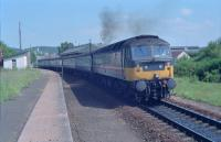 47642 leaves Forres with an Aberdeen-Inverness train on a sweltering day in the summer of 1990. This was during the period when Sprinters were withdrawn not long after their introduction. The former Perth platform was to the right of the locomotive. The photograph is taken from the former eastbound (Inverness to Aberdeen) platform.<br><br>[Ewan Crawford&nbsp;//1990]