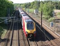 A southbound Virgin Voyager has just descended the 10 miles from Beattock Summit as it approaches Beattock village at speed on 27 May 2012. On the right the stub of the former Moffat branch can be seen.<br><br>[John McIntyre&nbsp;27/05/2012]