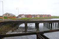 A dreich June day in 2012, looking across the cut - down remains of North Blyth staithes to the former railway settlement of that name. The building on the left is North Blyth WMC, once the BR Staff Assoc Club. The nearest street is named Worsdell Terrace (of J27 fame). The former steam shed was located to the left of the Club. It's diesel depot replacement was located at Cambois, a further mile to the left. The pedestrian ferry that ran from this point across the river to the town of Blyth was withdrawn in the 1980's - it is now many miles by road between the two settlements. <br><br>[Brian Taylor&nbsp;15/06/2012]