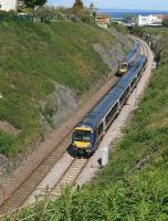 Two class 170 units pass between Kinghorn Tunnel and the station on 19 June. The cutting had been cleared of vegetation and stabilised earlier this year. In the background is the Art Deco former <I>Regal</I> cinema.<br><br>[Bill Roberton&nbsp;19/06/2012]
