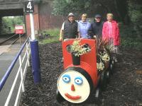 Less than a year after their adoption of Crookston Station, the 'Friends of Rosshall Park and Gardens' have recently taken delivery of a barrel train planter supplied by Glasgow City Council and planted with the help of their apprentices. Some of the 'Friends' are seen standing alongside the new addition on 21 June 2012. [See image 35831]<br><br>[John Yellowlees 21/06/2012]