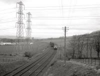 A Largs bound DMU working wrong-line passing a PW train on the morning of Easter Sunday 1963, during reballasting work at Kilruskin cutting, near West Kilbride. [See image 36606]<br><br>[R Sillitto/A Renfrew Collection (Courtesy Bruce McCartney)&nbsp;14/04/1963]