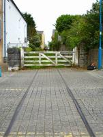 Extant track and crossing gates on Gordon Street, Pembroke Dock, looking east along trackbed that passes between the houses in the distance and crosses Water Street to access the station some 50 metres beyond [see image 39622].  <br><br>[David Pesterfield&nbsp;23/05/2012]