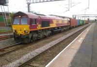 66041 and its containers make a colourful sight at Nuneaton on 29 June as the train snakes between the platform 4 through route and platform 1 (Coventry line). At least one down passenger train was slowed to allow this relatively rare conflicting movement.<br><br>[Ken Strachan&nbsp;29/06/2012]
