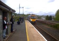 The 12.28 to 'Oxenholme and all connections everywhere' coasts into Kendal under a glowering sky, with the mountains of the Lake District in the background. [see image 25577 for a view looking the other way]<br><br>[Ken Strachan&nbsp;13/05/2012]