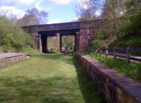 Several stations on the former 'back road' from Macclesfield [see image 39173] to Marple via Bollington are now informal picnic areas. This view looks North-West through one of the many bridges which had to be strengthened with an additional central support. The bushes on the left are close to the divergence of a former colliery tramroad.<br><br>[Ken Strachan&nbsp;12/05/2012]