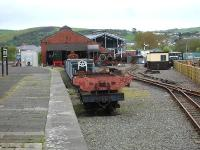 The Vale of Rheidol Railway's old Aberystwyth steam shed seen beyond the former bay platform end in May 2012, with the new VoR platform line and run round loop on the right. The new stabling and heavy maintenance facility can be seen under construction beyond the rear of the steam shed. Nearest the camera on the flat wagon is the main frame for VoR No7 Owain Glyndwr which is awaiting completion of the new facility to allow rebuilding to be started.<br><br>[David Pesterfield&nbsp;10/05/2012]