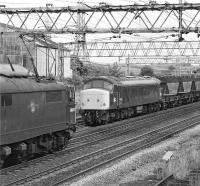 76022 heads through Penistone towards Sheffield in July 1981 with a train of scrap from Dewsnap Sidings in Dukinfield. Meantime 45001, employed that afternoon on trip workings between Penistone and Dodworth Colliery, is about to shunt a half-load of power station coal into the sidings at Barnsley Junction.<br><br>[Bill Jamieson&nbsp;17/07/1981]