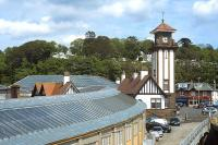 Looking over Wemyss Bay station from the 15.00 ferry departure for Rothesay on 1 June 2012. The covered walkway linking the railway station and the ferry terminal is prominent in the left foreground.<br><br>[Bill Jamieson&nbsp;01/06/2012]
