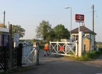 The signalman at Swinderby station manually opens the level crossing gates after an oil train from Immingham has passed through. The busy road is narrow at this point but the distance between the two gates is substantial leading to an unusual arrangement when the crossing is open to road traffic. [See image 16453]<br><br>[Mark Bartlett&nbsp;22/05/2012]