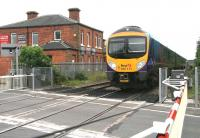 Shortly after leaving Northallerton station on 9 July, the 11.35 Manchester Airport - Middlesbrough has turned north east onto the former Leeds Northern route heading for Teesside. The train is about to run over Low Gates level crossing on the busy A167, with the town's High Street off to the left. The kitchen showroom on the up side was once Northallerton Town station, opened by the Leeds Northern Railway in June 1852 and closed less than 4 years later on 1 January 1856.   <br><br>[John Furnevel&nbsp;09/07/2012]