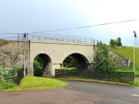 View east at Tomatin distillery in July 2012 showing the bridge carrying the Highland Main Line over the distillery access road and the adjacent burn. The signal for the north end of Tomatin loop can also be seen.<br><br>[Mark Bartlett&nbsp;05/07/2012]