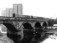 A train from Glasgow Central crossing the River Ayr on the approach to Ayr station in March 1972.<br><br>[John Furnevel&nbsp;02/03/1972]