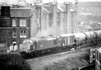 A southbound cement train crossing the bridge over Gorgie Road and approaching the site of Gorgie East station on the Edinburgh sub on 14 April 1981.<br><br>[John Furnevel&nbsp;14/04/1981]