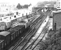 A westbound mixed freight approaching Southampton Central in July 1981 behind a class 33 locomotive, with passenger trains occupying both up platforms.<br><br>[John Furnevel&nbsp;06/07/1981]
