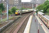 The west end of the busy Dalmuir station in July 2005, with a Balloch - Airdrie train approaching the station about to pass a recently terminated service from Motherwell standing in bay platform 5.<br><br>[John Furnevel&nbsp;27/07/2005]