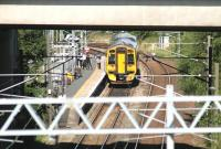 The 12.17 train to Waverley waits alongside the platform at Newcraighall station on 20 August 2012. Long lens view from Whitehill Road at the north end of Millerhill Yard, looking under the bridge carrying the A1.<br><br>[John Furnevel&nbsp;20/08/2012]