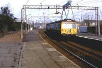 311102 drawing into Port Glasgow with a service for Glasgow Central, sometime in 1980. Note the old footbridge still in place to the left. This provided access to the station and crossed the bay platform once used by Wemyss Bay trains. [See image 22579]<br><br>[Graham Morgan Collection&nbsp;//1980]