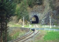 Le Tunnel de Besse, 110 metres long, lies between Saint Sauveur la Sagne and Saint Alyre d'Arlanc on the AGRIVAP tourist line in the Auvergne region. Usually a big hit with passengers pulled along in an open wagon behind the line's heritage Panoramique railcar X4208, the tunnel is seen here pre-season on a quiet Saturday morning over the level crossing of the D38 road.<br><br>[Andrew Wilson&nbsp;28/04/2012]