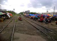 Market day at Taguig, right next to the PNR main line to Alabang [see image 40401]. Notice the market stalls built onto motorbike sidecars; the practical addition of umbrellas; and the skate (in the distance) on the right hand track. Skates are home-built powered wagons, privately owned and operated. They provide a useful service to the public, but contribute nothing to PNR; and can be rather dangerous, as they have no formal collaboration with the PNR working timetable. Understandably, they are not easy to photograph; especially up close.<br><br>[Ken Strachan&nbsp;28/08/2012]