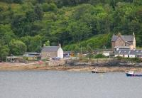 Stromeferry station, as seen across tidal Loch Carron, from Strome Castle on the north bank. 158705 has just called on its way to Inverness with the 1715hrs from Kyle. In front of the station is the slipway of the old car ferry, replaced by the A-road from Strathcarron in the 1960s. <br><br>[Mark Bartlett&nbsp;10/07/2012]