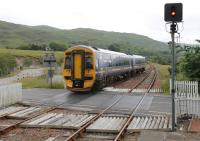Inverness based 158715 crosses the A890 main road as it leaves Strathcarron heading for Kyle of Lochalsh. From here the road runs alongside the railway almost all the way to Stromeferry with a number of vantage points. <br><br>[Mark Bartlett&nbsp;11/07/2012]