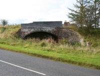 Looking west across the A6105 at  Greenlaw on 6 October 2012 to the long abandoned bridge that once carried the road over the Berwickshire Railway. The chimneys of the former station, now a private residence, can be seen rising above the embankment. Greenlaw station closed in 1948 along with the route east towards Duns, although the line west to Ravenswood Junction remained open until 1965 [see image 34992].<br><br>[John Furnevel&nbsp;06/10/2012]